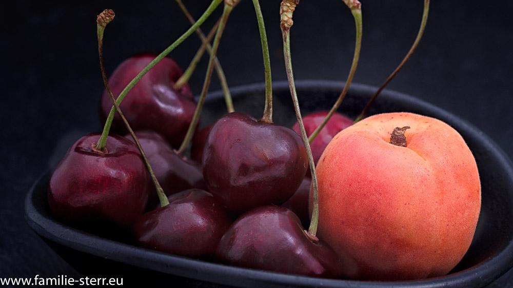 Kirschen und Aprikose in einer dunklen Schale