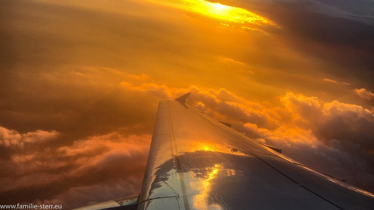 Wolken und Sonnenuntergang auf dem Flug von Berlin Tegel nach München, Blick über die Tragfläche und das Triebwerk