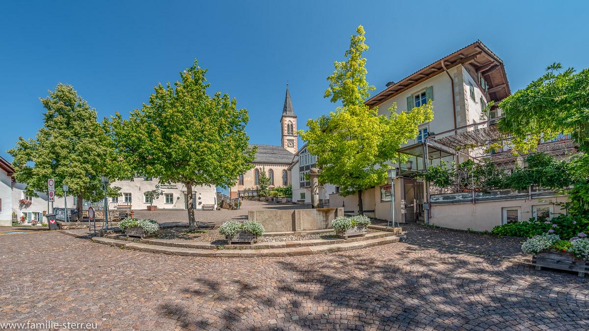 Dorfplatz von Aldein in Südtirol mit Dorfbrunnen und Kirche im Hintergrund