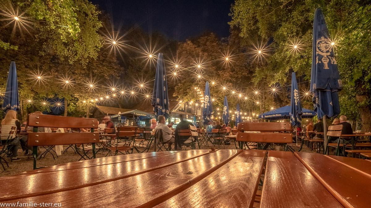 Lichterketten strahlen über dem nächtlichen Biergarten Inselmühle in München Untermenzing