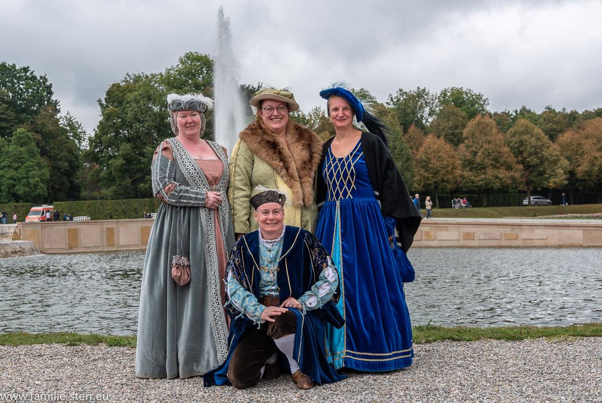 Gruppe von 4 Burgfräulein in historischen Kostümen vor der Fontäme im Schlosspark Oberschleißheim