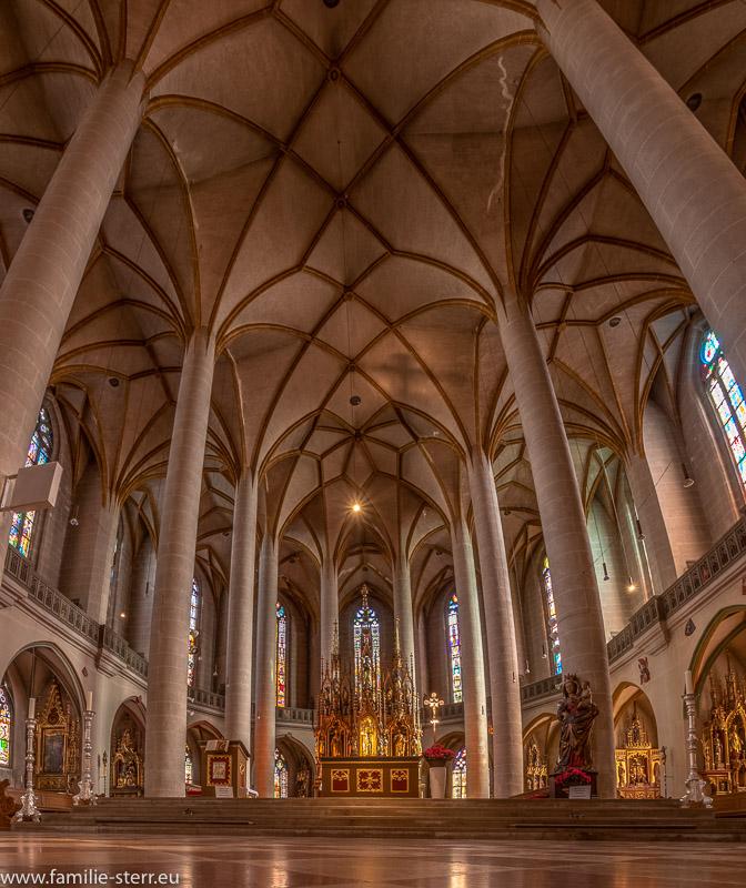 Blick nach oben in der Gewölbe und in den Altarraum mit den bunten Fenstern der Basilika St. Martin in Amberg in der Oberpfalz