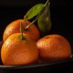 drei Clementinen in einer schwarzen Schale