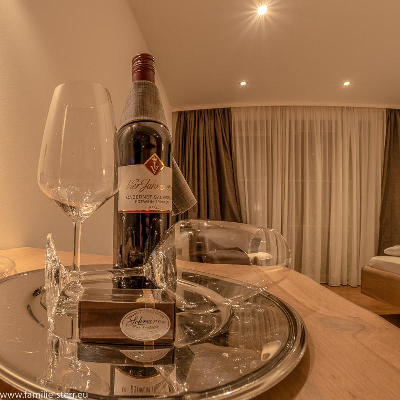 eine Flasche Rotwein und Pralinen als Gastgeschenk im Heimatzimmer des Hotel Das Reiners in Grafenau