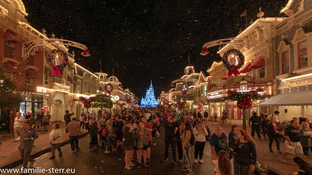 ein Blick über die nächtliche Main Street USA mit unglaublich vielen Menschen und künstlichem Schnee zum beleuchteten Schloss am Ende im Magic Kingdom Themenpark