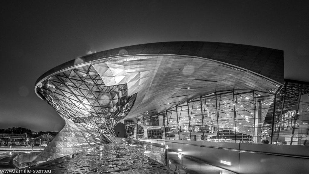 Blick auf die BMW - Welt von der Brücke zum BMW - Museum aus in einer regnerischen Nacht