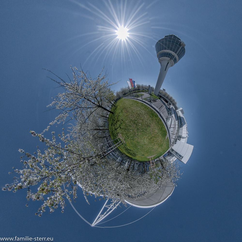 blühende Bäume neben dem Tower am Flughafen München als Little Planet
