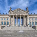 Vorderansicht des Berliners Reichstagsgebäudes mit wehender Deutschlandfahne bei leichter Bewölkung am blauen Himmel