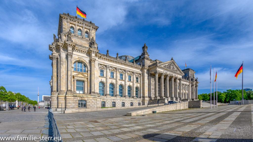 Seitliche Sicht aut das Berliners Reichstagsgebäude mit wehender Deutschlandfahne bei leichter Bewölkung am blauen Himmel