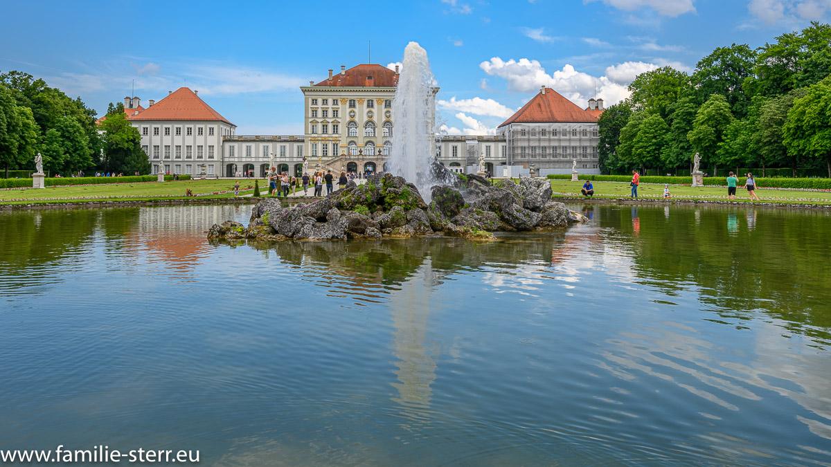 Brunnen vor dem Schloss Nymphenburg vor blau-weißem Himmel