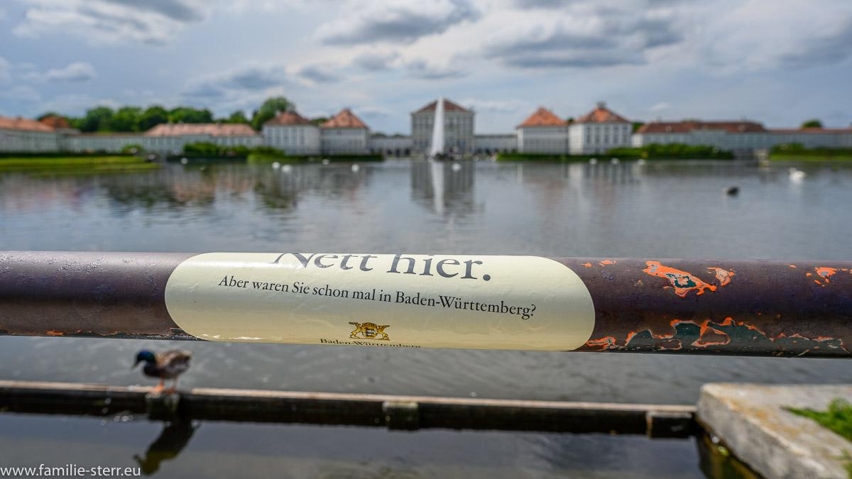 """Aufkleber """"Nett hier - aber waren sie schon einmal in Baden Württemberg"""" am Platz vor dem Schloss Nymphenburg"""