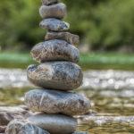 glitzerndes Wasser hinter einem Steinmännchen an der Isar bei Lenggries