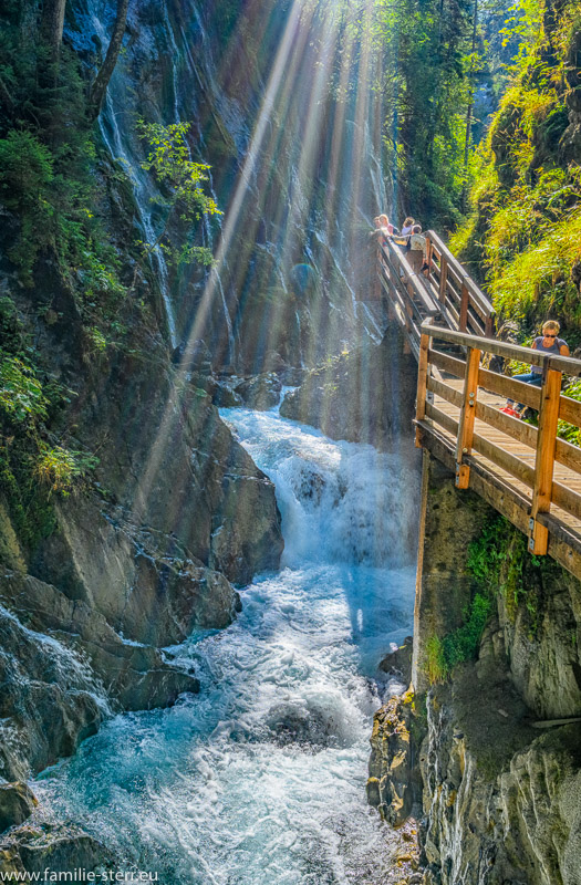 Sonnenstrahlen scheinen in die Klamm des Wimbach beim Ramsau und beleuchten den herbstlichen Wasserfall