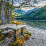 Picknicktisch am Ufer des Antholzer Sees an einem sonnigen Herbsttag