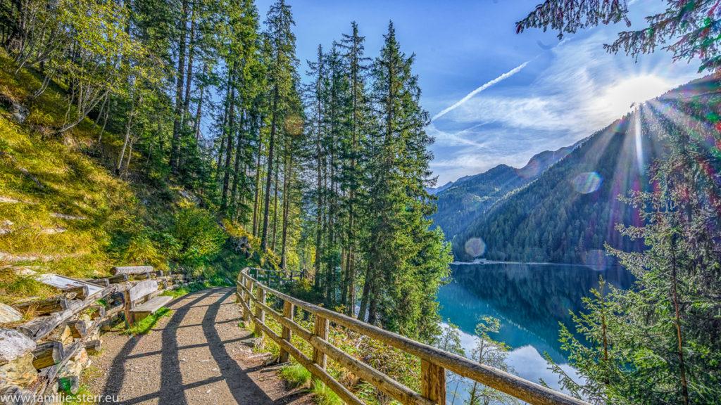 Weg am Ufer des Antholer Sees in Südtirol an einem Sonnentag im Herbst