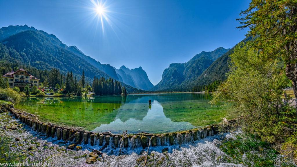 Die Berge am Rand des Toblacher Sees spiegeln sich im grünen Wasser des Sees
