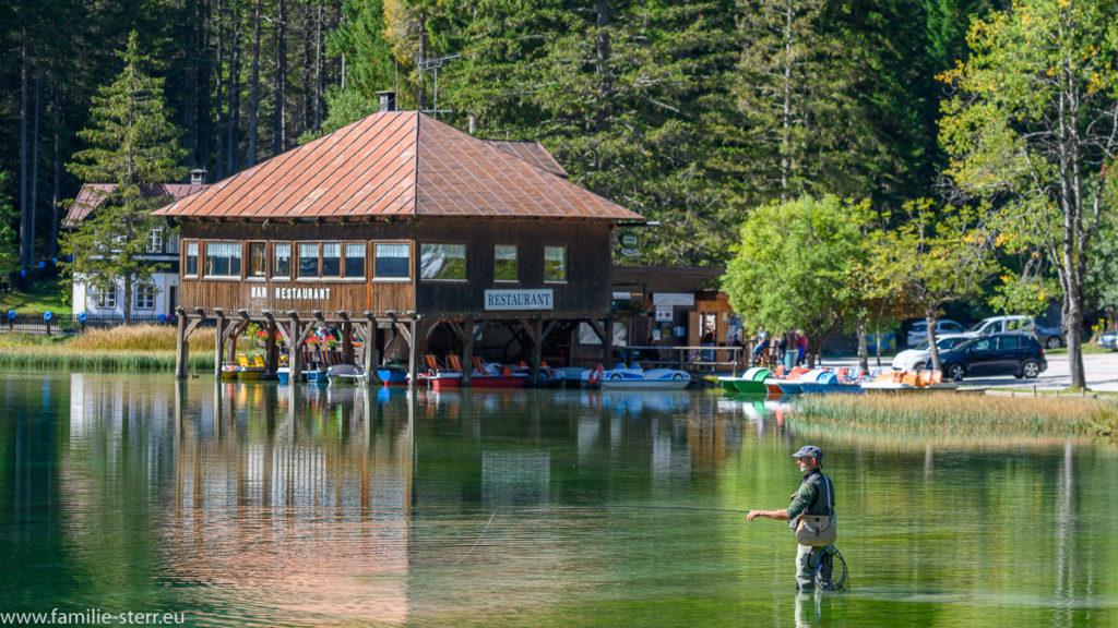 Restaurant im Toblacher See in Südtirol bei strahlendem Sonnenschein mit einem Fliegenfischer im Wasser