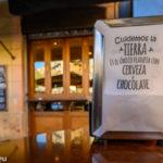 """Serviettenbox auf einem Tisch vor einer Tapas - Bar in Barcelona mit dem Aufdruck """"Cuidemos la Tierra, es el unico Planeta von Cerveza y Chocolate"""