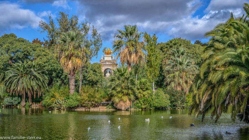 Blick über den See im Parc De La Ciutadella durch Palmen auf die Cascada Monumental Barcelona