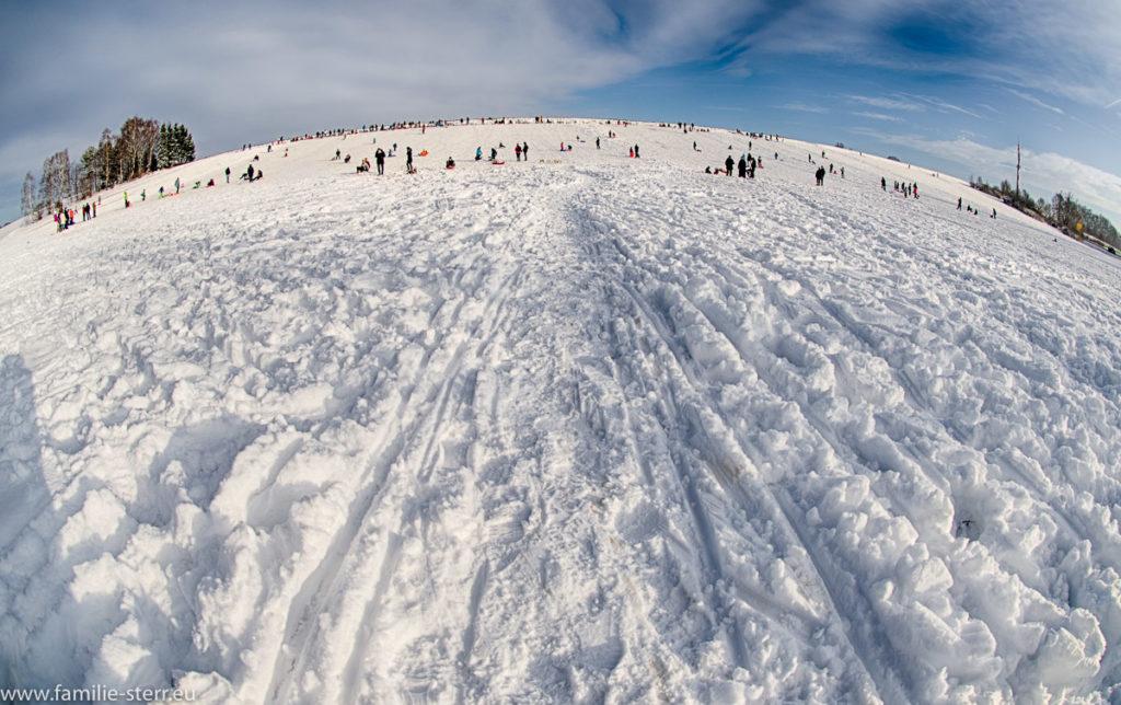 der schneebdeckte Fuchbserg in Erding mit vielen Schilttenfahrern