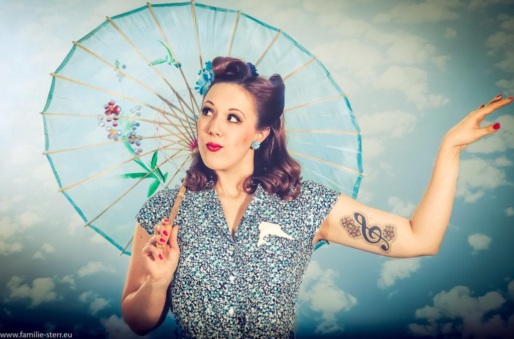 Burlesque - Workshop - junge Frau mit Sonnenschirm vor wolkigem Himmel