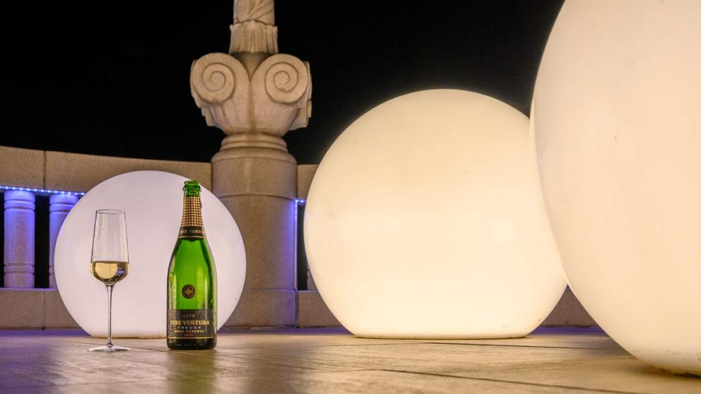 Flasche Cava Tresor und ein Glas Casa vor der beleuchteten Dekoration der Rooftop Bar im Hotel Casa Fuster in Barcelona