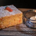 ein Stück Karottenkuchen im Schein eines Teelichts
