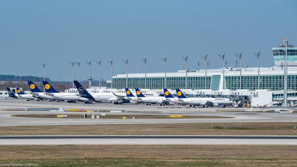 eine Reihe von Lufthansa - Flugzeuge parkt vor dem Satelliten am Terminal 2 am Flughafen München