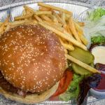 Hamburger mit Bacon und Käse, dazu Pommes als Beilage
