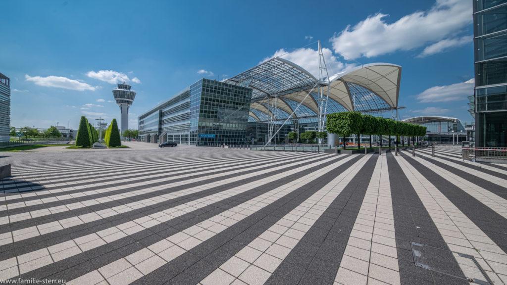 Blick vom Vorplatz des Terminal 2 mit Tower und Munich Airport Center MAC bei strahlendem Himmel