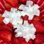 Erdbeeren mit 3 Sahnehäubchen in einer roten Schüssel