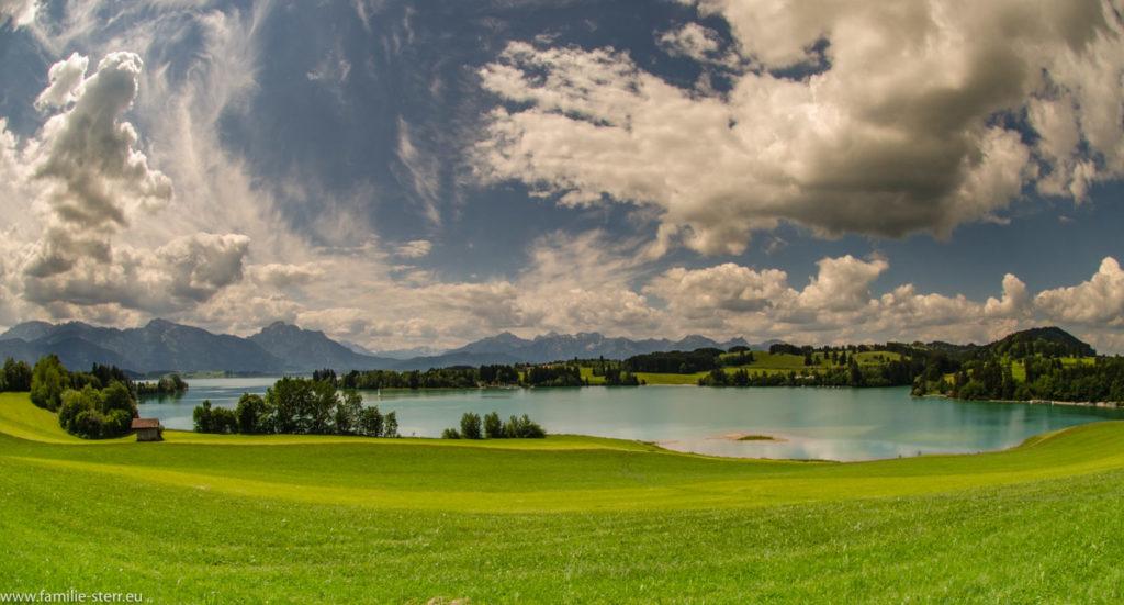 Blick über den Forggensee in die bayerischen Alpen mit weißen Kumuluswolken im weiß-blauen Himmel