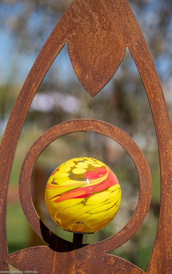 gelbe Glaskugel in einem verrosteten Gestell