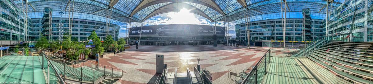 menschenleeres Forum des Munich Airport Center mit Blick auf das Terminal 2 und in den strahlenden Sonnenschein während der Corona Pandemie