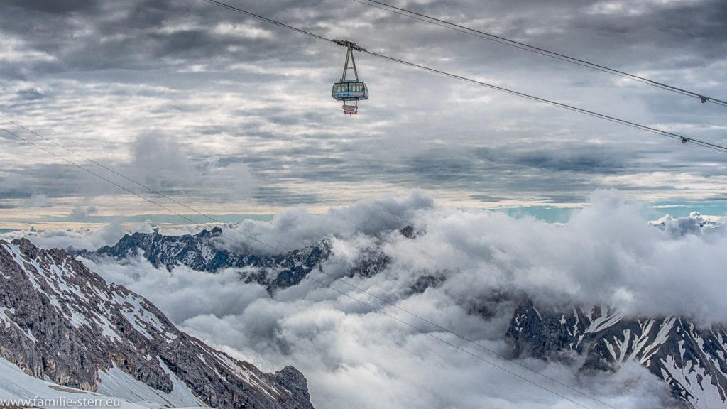 Gondel der Seilbahn von der Zugspitze zum Zugspitzplatt schwebt über tiefhängenden Wolken