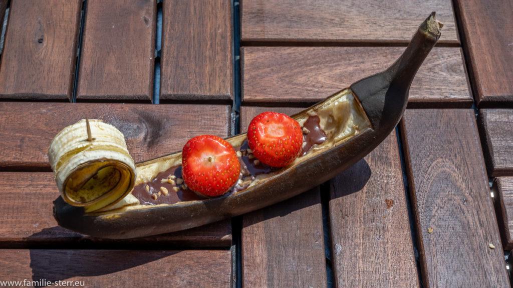 eine gegrillte Schoko - Banana mit Erdbeeren und Haselnüssen in Form einer venezianischen Gondel