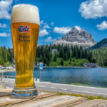 ein frisches Glas Weißbier vor dem Lago di Misurina und den Drei Zinnen in den Südtiroler Dolomiten