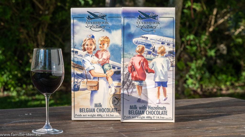 2 große 400gr - Tafeln belgische Schokolade in Verpackungen mit Flugzeug - Motiven (Vollmilch und Haselnuss) und dazu ein Glas Rioja