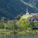 Blick über den Mühlwald - Stausee auf den Ort mit der auf einem Hügel thronenden Kirche