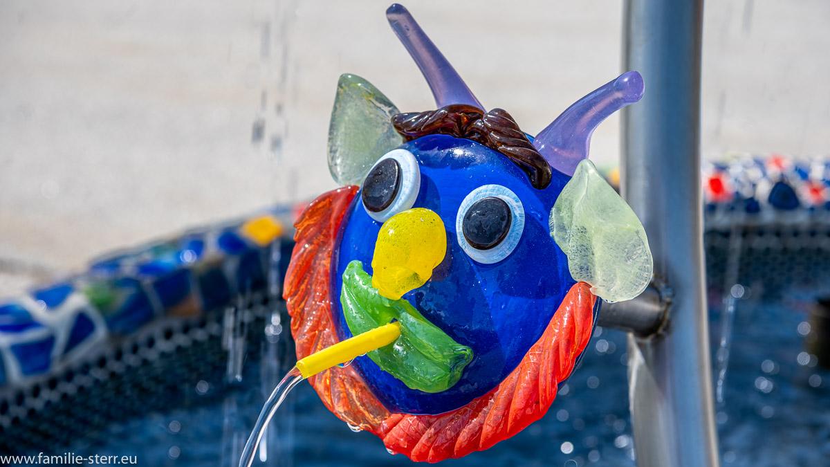 eine gläsernes Gesicht als Wasserspeier an einem Brunnen in der Josua Glaswelt