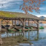 ein altes Bootshaus mit Ruderbooten am herbstlichen Alpsee
