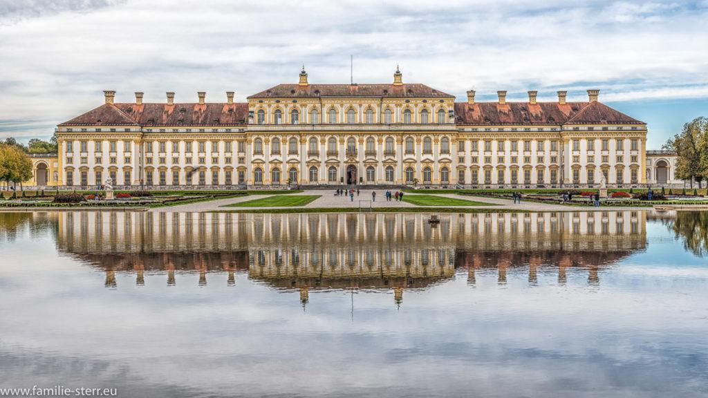 Die Ostfassade des Neuen Schloss Oberschleißheim spiegelt sich im Wasser der Kaskade im Schlosspark