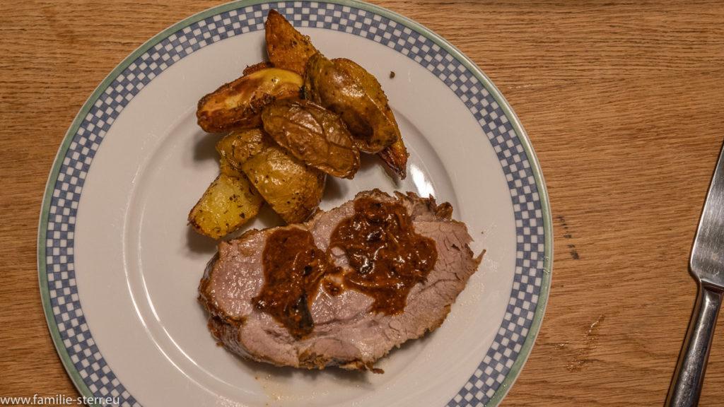 der fertige Teller mit einer Scheibe Schweinbraten, etwas brauner Soße daraus und ein paar Rosmarinkartoffeln als Beilage