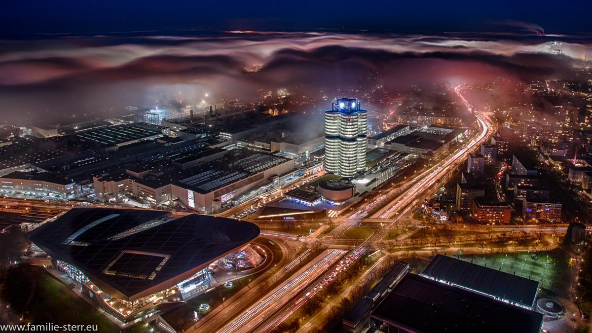 Eine Nebelwolke umhüllt das nächtlich beleuchtete BMW Hochhaus und die BMW - Welt