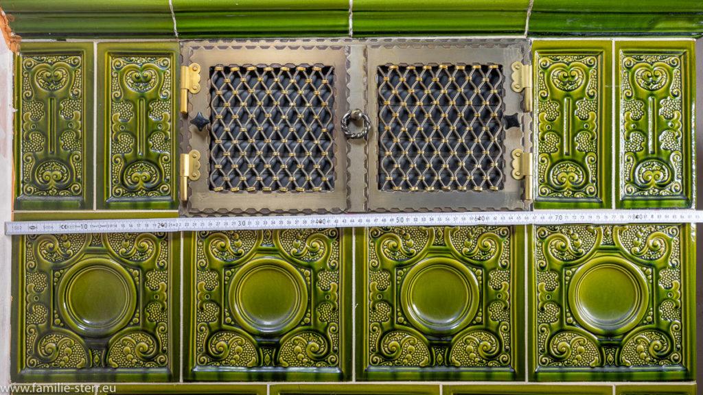 traditioneller Kachelofen mit grünen Fliesen und vielen Ornamenten