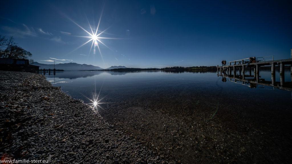 strahlende Sonne und blauer Himmel über dem spiegelglatten Chiemsee am Strandbad Breitbrunn auf der Halbinsel Urfahrn