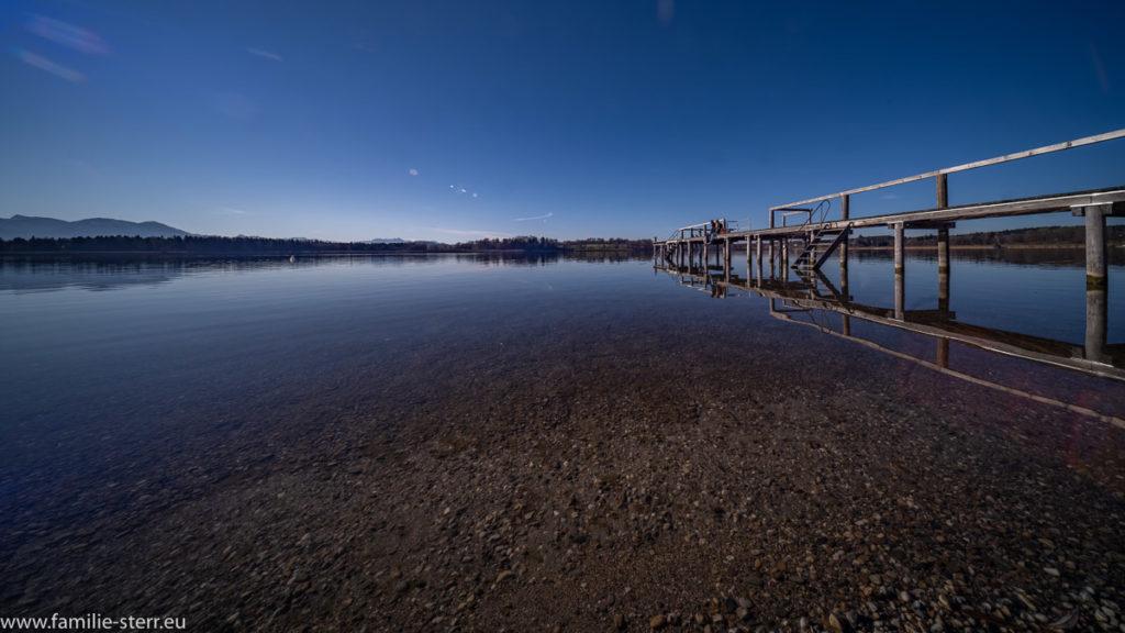 spiegelglattes Wasser vor dem Strandbad Breitbrunn mit dem Steg am rechten Bildrand