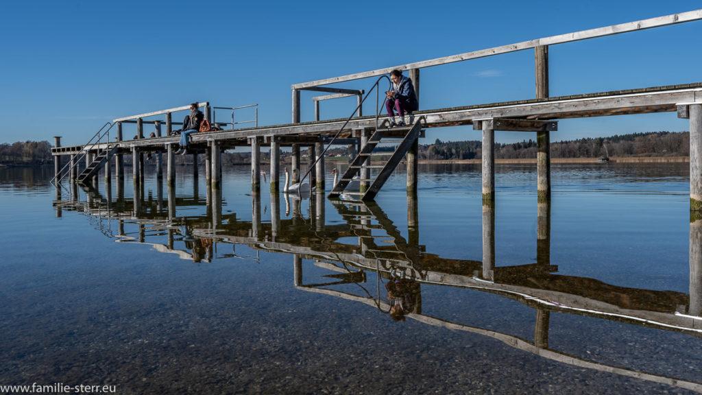 der Steg des Strandbads Breitbrunn am Chiemsee spiegelt sich im Wasser