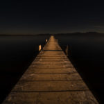 ein langer, leuchtender Steg führt auf den dunklen See und in die dunklen Berge