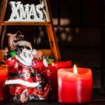 Christbaumfigur in Form eines singenden Weihnachtsmanns vor drei Adventskerzen